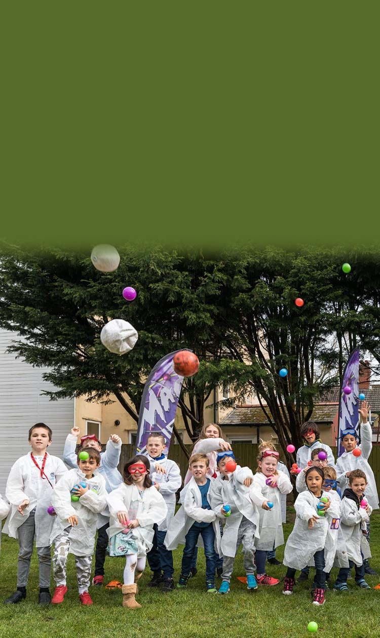 Kids in mad science lab coats throwing colored balls