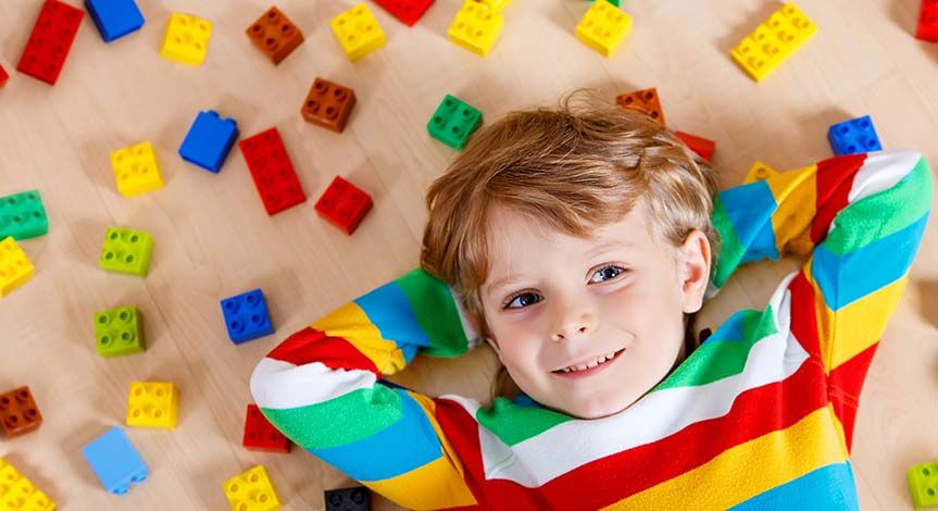 Boy lying on the floor in colorful striped shirt lying on Lego
