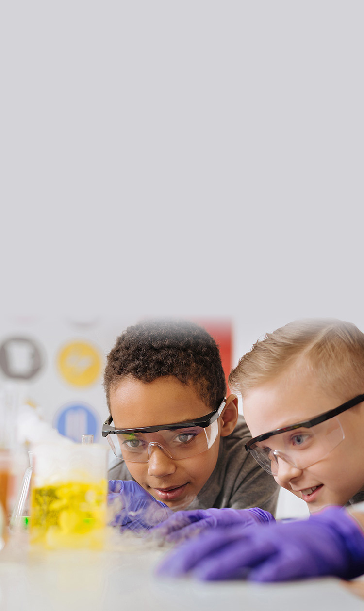 boys in safety goggles leaning closely to the table and watching chemical reaction going on in the beaker